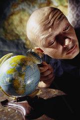 Hamburg  Deutschland  glatzkoepfiger Mann horchend an einem Globus