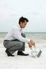 Man crouching on beach using broom and dustpan