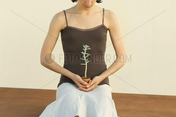 Woman holding potted plant on lap  cropped view