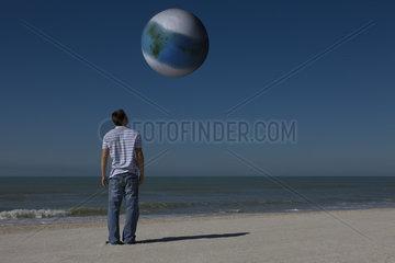 Man on beach looking up at alien world orbiting overhead