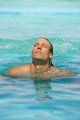 Swimmer surfacing  eyes closed  head back