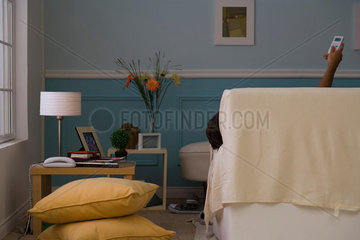 Person reclining on sofa controlling air conditioner with remote control  rear view