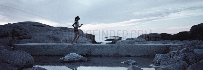 Woman running across footbridge near seashore in early morning