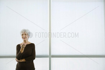 Senior woman standing with hand out  smiling at camera