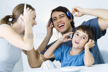 Family listening to CD player together  father and son using wireless headphones