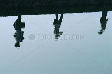 Reflection of three figures walking at water's edge