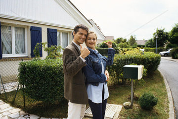 Couple standing in front of house  making thumbs up gesture at camera