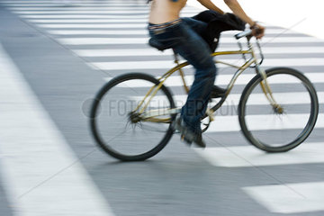 Person riding bicycle over crosswalk