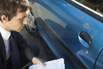 Insurance adjuster examining damage to car exterior