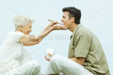 Senior woman feeding adult son takeout food with chopsticks  side view