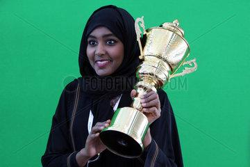 Dubai  Vereinigte Arabische Emirate  Frau in Landestracht haelt einen Pokal in den Haenden