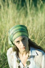 Young woman wearing scarf around head  in field  portrait
