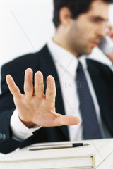 Businessman on phone call  making stop gesture with hand