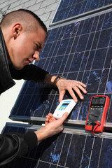 Berlin  Deutschland  Auszubildender misst Solarstrom eines Solar-Panels