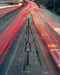 Lichtspuren von Fahrzeugen an einer Stadtautobahnausfahrt in der Daemmerung