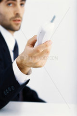 Businessman holding out cordless phone