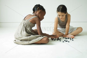 Two girls sitting on the ground playing with marbles