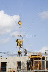 Construction workers guiding bucket suspended by crane to deposit concrete on building under construction
