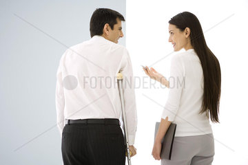Two office colleagues talking  one using crutches