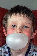 Berlin  ein Junge macht eine Kaugummiblase