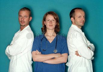 Eine Medizinerin steht zwischen zwei Aerzten