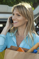 Woman using cell phone and carrying bag of groceries