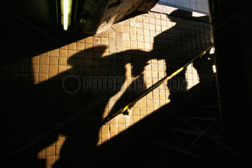 Men's shadows on stairwell wall