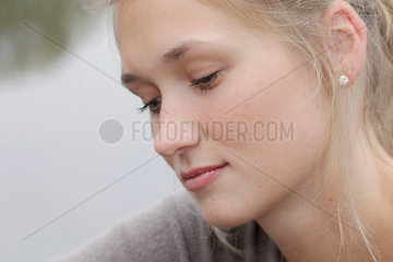Blonde junge Frau  23 Jahre alt  schau nachdenklich zur Seite. (model released)