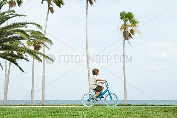 Boy riding bicycle at the beach  side view