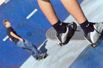 Skateboarder perched at edge of ramp watching friend skate on ramp below