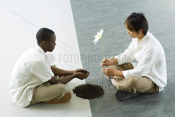 Two males sitting face to face on ground  one holding out handful of soil  the other holding out a flower