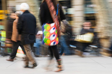 Pedestrians walking on sidewalk  blurred