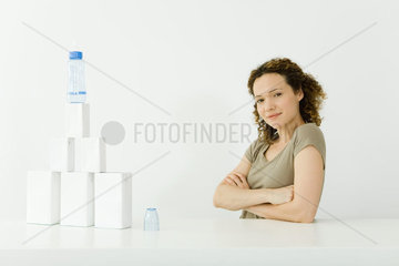 Woman beside stacked milk cartons and baby bottle  arms folded  smiling at camera