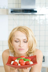 Woman contemplating plate of Caprese salad  looking down