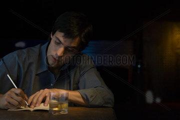 Man writing in notebook  sitting in bar