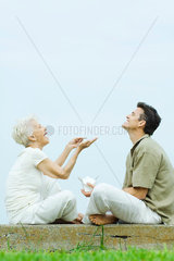 Senior woman and adult son sitting face to face on the ground  sharing takeout food  laughing
