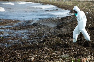 Person in protective suit walking along polluted shore