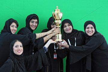 Dubai  Vereinigte Arabische Emirate  Frauen in Landestracht halten einen Pokal in den Haenden