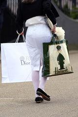 Ascot  Grossbritannien  Frau traegt Tueten von Dior und Harrods