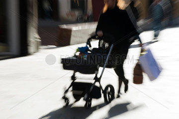 Pedestrian pushing baby carriage on sidewalk  carrying shopping bags  blurred
