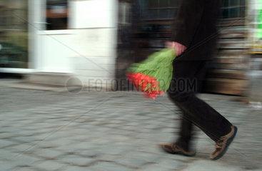 Berlin  Mann mit Tulpenstrauss laeuft die Strasse entlang