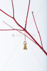 Miniature Buddha ornament hanging from bare branch