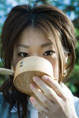 Female drinking from traditional Japanese hishaku ladle  close-up
