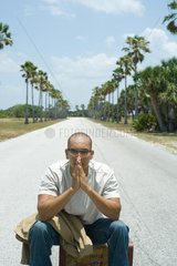 Man sitting on suitcase in the middle of road  eyes closed  hands clasped in front of face