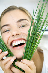Woman holding chives up to face  smiling  laughing