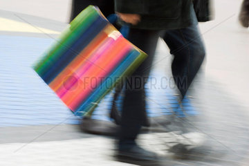 Pedestrian carrying shopping bag  blurred