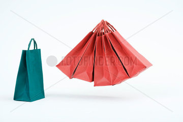 Group of red shopping bags floating in midair beside single blue bag