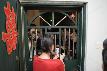 Chinese wedding door tradition  female handing cup to group of men through barred door  rear view