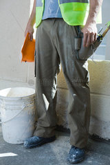Consturction worker holding hard hat standing by bucket  low section