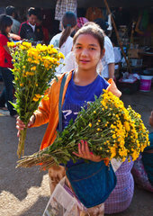 Young Burmese woman selling flowers at the CENTRAL MARKET in KENGTUNG also known as KYAINGTONG  MYANMAR